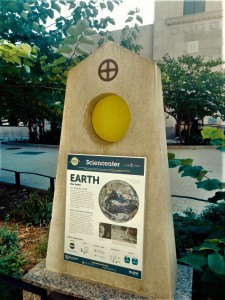 A estação da Terra. Estas estações estão localizadas no Commons, o coração do centro de Ithaca. As aberturas circulares no alto das estações representam a circunferência solar e servem para uma comparação com as circunferências planetárias.